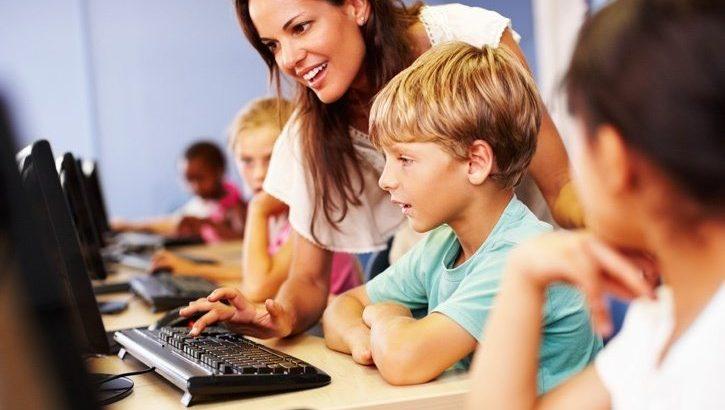 Teachers teaches students on computer